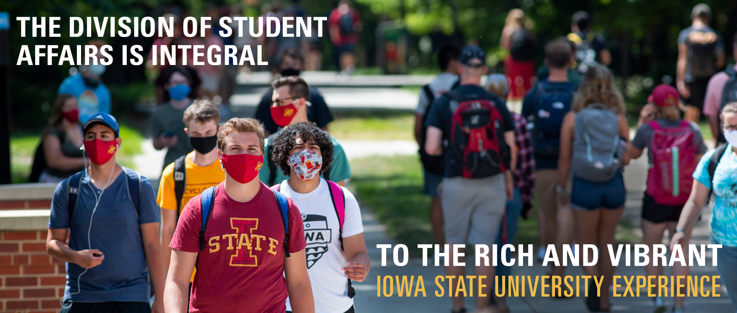 Students with masks on walking on campus